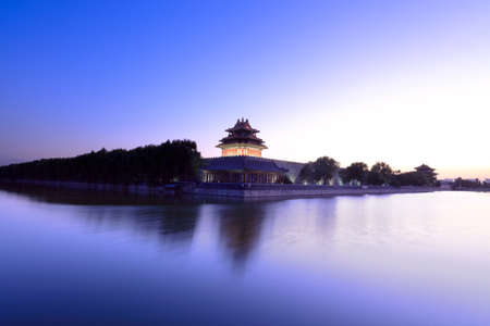 the turret of beijing forbidden city at dusk with moat