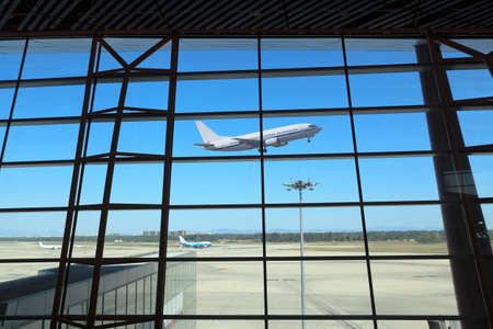 departing: flight departing,the looking glass of modern airport terminal Editorial