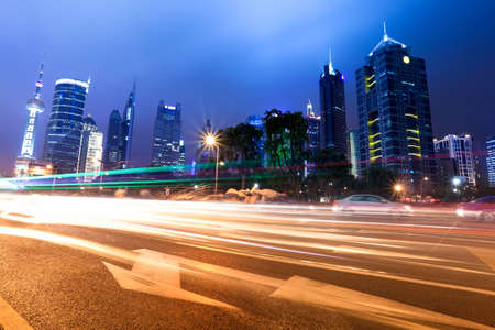 light trails on the modern building background at night in shanghai,China. photo