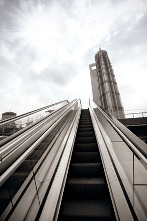 rise and shine: moving escalator in city outdoor under the sun Stock Photo