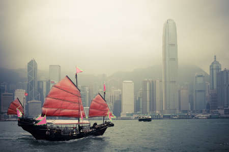 china landscape: traditional wooden sailboat sailing in victoria harbor,Hong Kong.