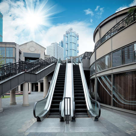 rise to the top: city outdoor escalator under the sun Editorial