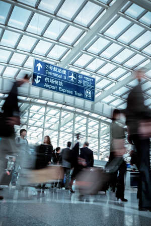 passenger motion blurred in modern airport hall