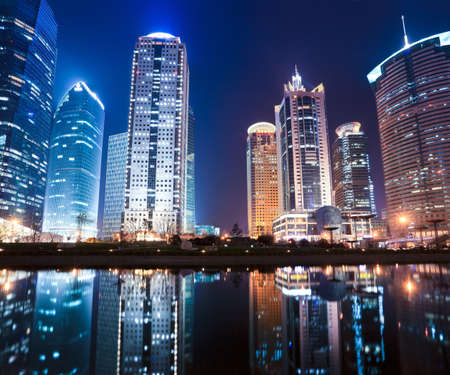 beautiful night view of modern buildings and reflection in shanghai photo