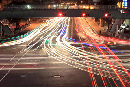 light trails on crossroad in rush hour traffic at night photo