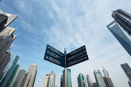 signpost with shanghai skyline of the lujiazui financial center at daytime photo