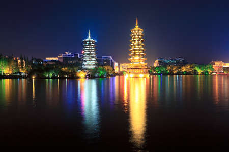 golden and silver pagodas in banyan lake at night,guilin,China photo