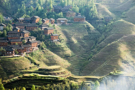china landscape: rice terraces and ethnic minority village at dusk in guangxi province,China