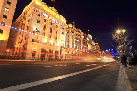the bund in shanghai at night,light trails on the street with classical buildings photo