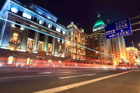 light trails on the street with classical buildings at night in shanghai photo