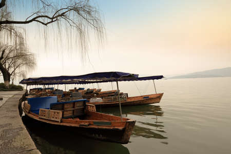 dream lake: beautiful scenery of the west lake,wooden boat is docked at the shore in hangzhou,China