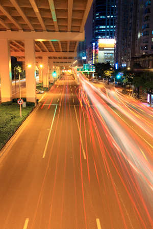 viaduct traffic at night with light traces from moving cars photo