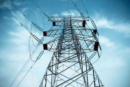 electricity pylon with cable silhouetted against blue sky photo