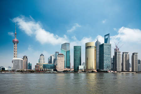 city scape: shanghai lujiazui financial center with huangpu river against a blue sky