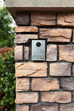 un campanello citofono e telecamera per visitatore sul muro di pietra Archivio Fotografico