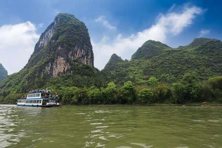 karst mountain landscape and pleasure boat in  lijiang river,guilin, China photo