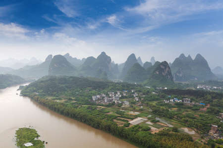 beautiful karst mountain landscape with turbid river in yangshuo photo
