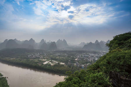 beautiful karst mountain landscape with sunlight through the clouds in yangshuo photo