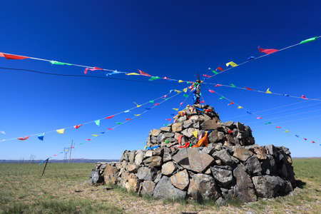praying stone and prayer flags on steppe in inner mongolia Stock Photo - 14673448