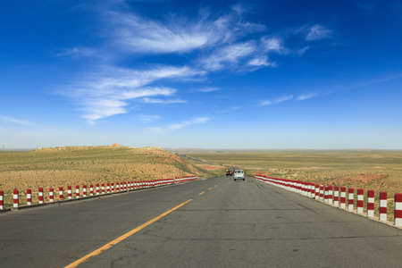 lonely road: desert road stretching to horizon in inner mongolia