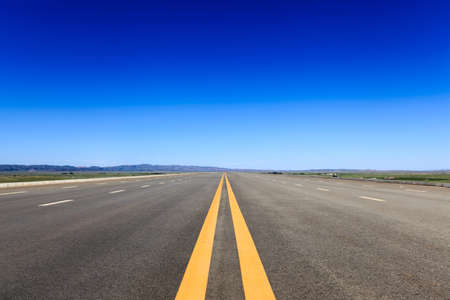 highway in steppe against a blue sky,long road stretching out into the distance photo