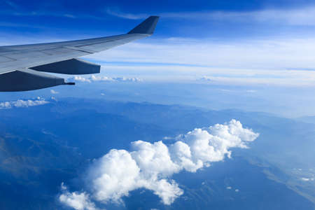 airfoil: view from airliner window with white clouds and mountain range