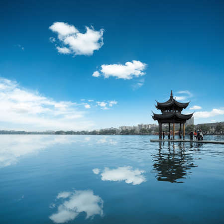bower: ancient pavilion against a blue sky and reflection in the west lake at hangzhou,China
