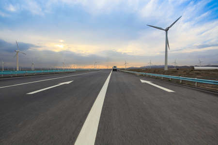 lonely road: highway with wind turbines generating electricity in sinkiang