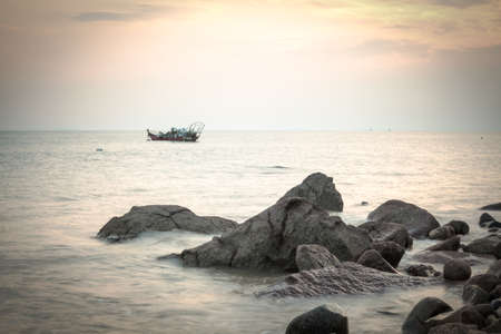 nightfall: beautiful dusk over the sea with reef and boat