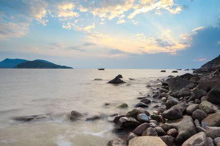 magnifique coucher de soleil sur la mer avec ciel dramatique et de galets