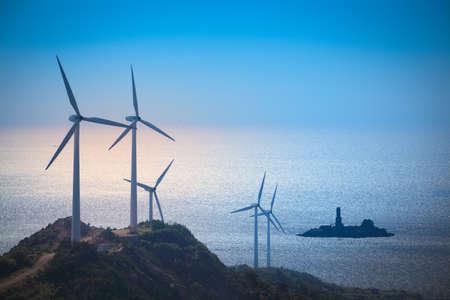 conservacion del agua: turbinas eólicas generan electricidad en la playa, fondo verde energía Foto de archivo