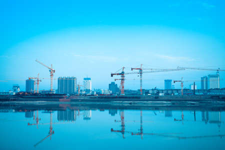 site construction: construction site reflection in the river,developing city background
