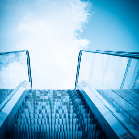rise and shine: escalator to blue sky on a city outdoor