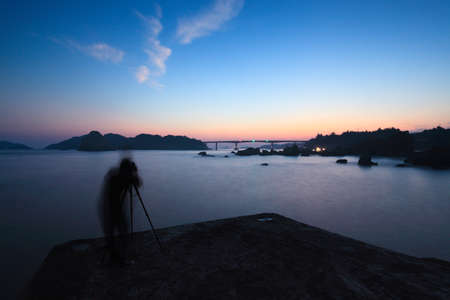 seaview: vague figure of a tourist with a camera on a sunset