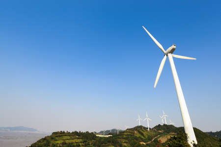 environmental conservation: wind turbines generating electricity in wind farm at the beach