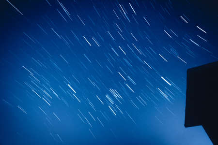 orbital: night sky with moving stars over the housetop Stock Photo