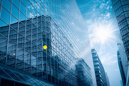 modern glass building under the blue sky with brilliant rays photo