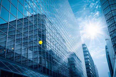 edificio corporativo: moderno edificio de cristal bajo el cielo azul con los rayos brillantes Foto de archivo