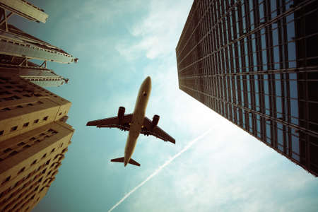 corporate airplane: airplane and modern buildings with dramatic sky,abstract cityscape Stock Photo
