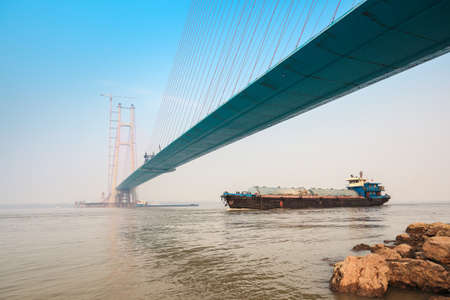 inland: a cargo ship on the yangtze river with construction of cable stayed bridge
