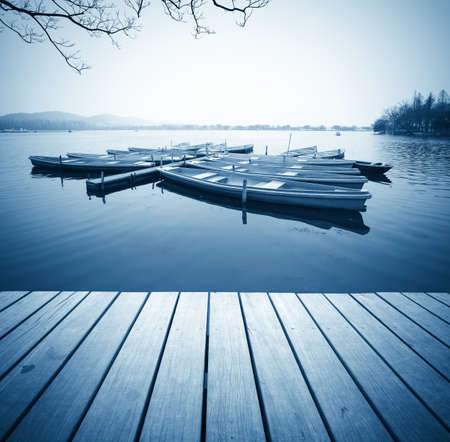 beautiful scenery in hangzhou,wooden floor with some boats in the west lake,China photo