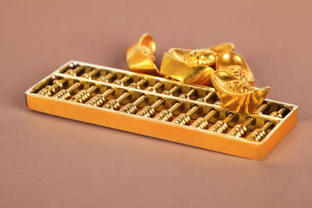 chinese golden abacus and gold ingots,traditional wealth concept background photo