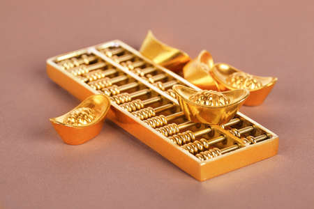gold ingot and golden abacus,traditional wealth concept background photo