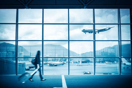delay: modern airport scene of passenger motion blur with window outside  Stock Photo