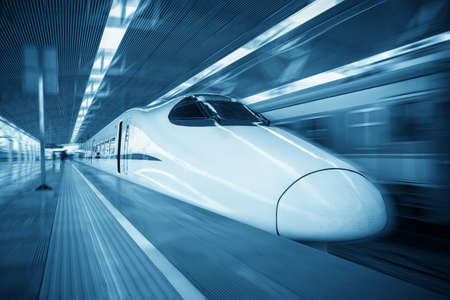 bullet train: modern high speed train passing railroad station with motion blur effect
