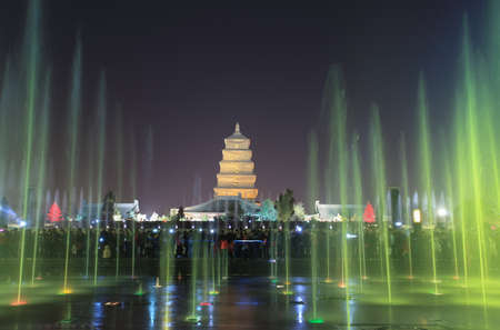 beautiful music fountain with giant wild goose pagoda at night in xian,China