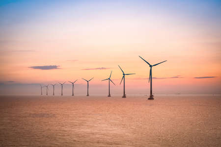 wind turbines: offshore wind farm at dusk in the east China sea. Stock Photo