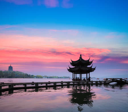 beautiful hangzhou in sunset, ancient pavilion silhouette on the west lake,China