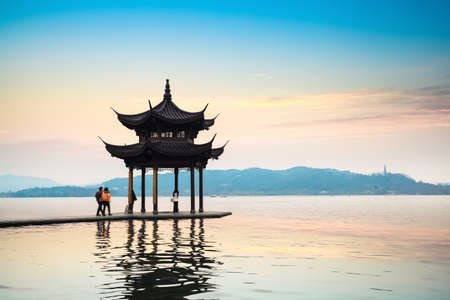 ancient pavilion reflection in the west lake at hangzhou with sunset glow,China Imagens - 21858782