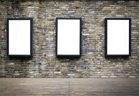 three blank billboards attached to a building exterior old brick wall photo